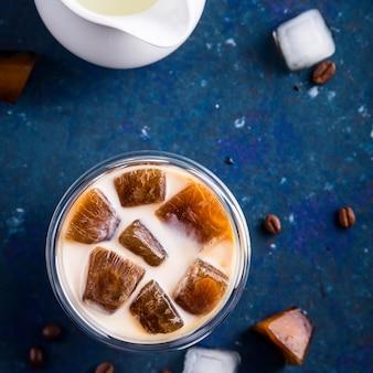 Bebida refrescante de verão frio com gelo e leite de café sobre uma mesa azul