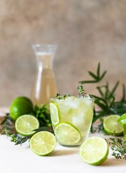 Bebida refrescante de verão ou limonada com limão e tomilho na superfície do concreto