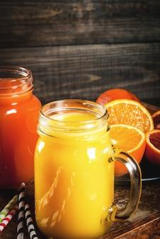 Bebida refrescante de verão suco de laranjas clássicas e laranjas sicilianas vermelhas em uma mesa de madeira rústica com laranjas inteiras e cortadas