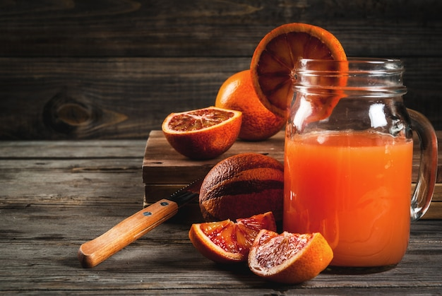 Bebida refrescante de verão. suco de laranjas sicilianas vermelhas. em uma mesa de madeira rústica, com laranjas inteiras e cortadas. copie o espaço