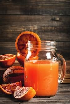 Bebida refrescante de verão suco de laranjas sicilianas vermelhas em uma mesa de madeira rústica com laranjas inteiras e cortadas