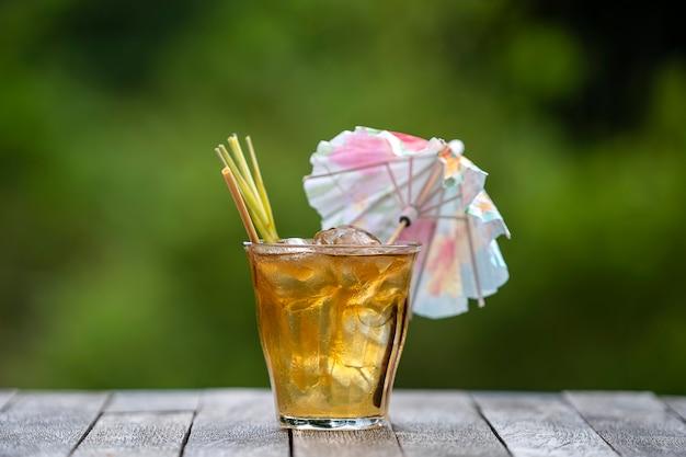 Bebida refrescante e saudável de canela e talos de capim-limão em uma mesa de madeira em um jardim tropical