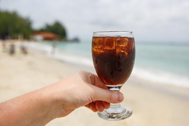 Bebida refrescante na mão na praia.