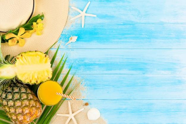 Bebida refrescante para o verão, suco de abacaxi tropical na luz de fundo azul madeira