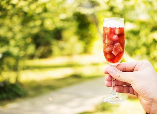 Bebida refrescante vermelha com frutas e gelo em uma mão