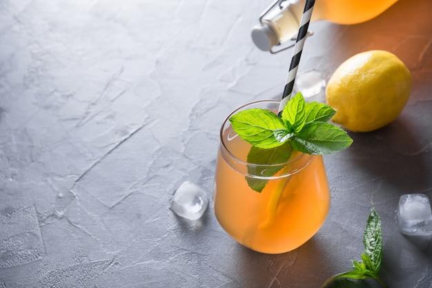 Bebida saboroso caseiro de kombucha na garrafa e no vidro com limão, hortelã.