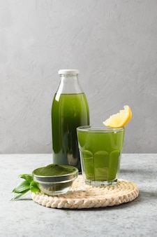 Bebida saudável de chlorella em vidro em um fundo cinza.