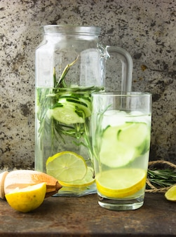 Bebida saudável de desintoxicação na moda. água de desintoxicação em garrafas com ingredientes, pepino, gengibre, limão, alecrim em fundo de metal. bebida de verão, limonada. dieta.