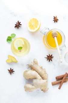 Bebida saudável do gengibre em um copo. raiz de gengibre, mel em uma jarra, limão em uma mesa branca.