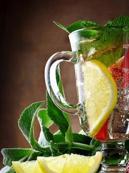 Bebida saudável do verão fresco com limão e morangos com gelo.