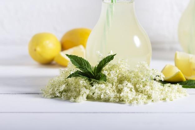 Bebida saudável e refrescante do verão da limonada mais velha. feche acima do xarope caseiro do elderflower em uma garrafa com elderflowers. bebida de verão hugo champagne bebe com calda de sabugueiro, hortelã e limão.
