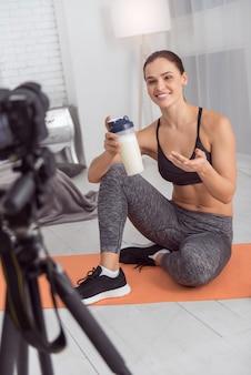 Bebida saudável. jovem blogueira atlética e bonita, de cabelos escuros, sorrindo e segurando uma bebida enquanto está sentada no tapete e fazendo um vídeo