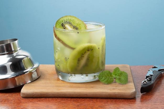 Bebida típica brasileira caipirinha com kiwi em mesa de corte de madeira