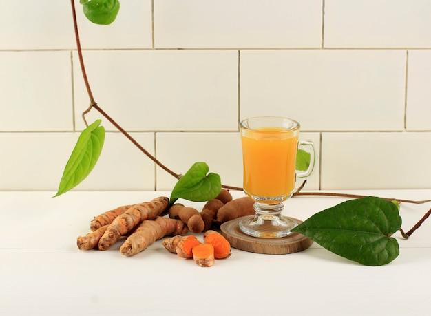 Bebida tônica energética com cúrcuma, gengibre, limão e mel em fundo branco, foco seletivo