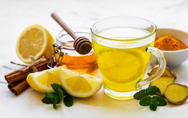 Bebida tônica energética com cúrcuma, gengibre, limão e mel em mesa de mármore branco