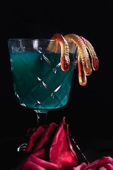 Bebida verde com vermes de geléia e rosas