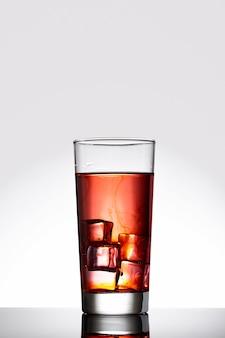 Bebida vermelha com cubos de gelo em copo