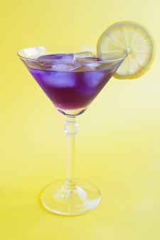 Bebida violeta gelada ou coquetel com limão em uma taça de martini no fundo amarelo. localização vertical. fechar-se.
