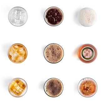 Bebidas alcoólicas em copos isolados em uma parede branca. coleção de cerveja e uísque.