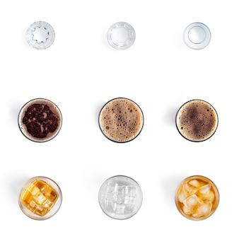 Bebidas alcoólicas em copos isolados em uma parede branca.