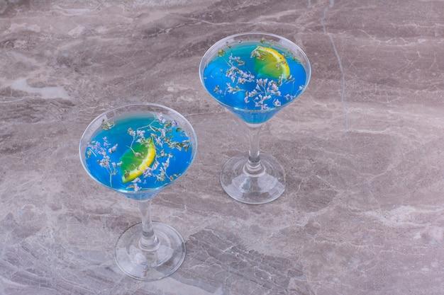 Bebidas azuis com cubos de gelo e limão.