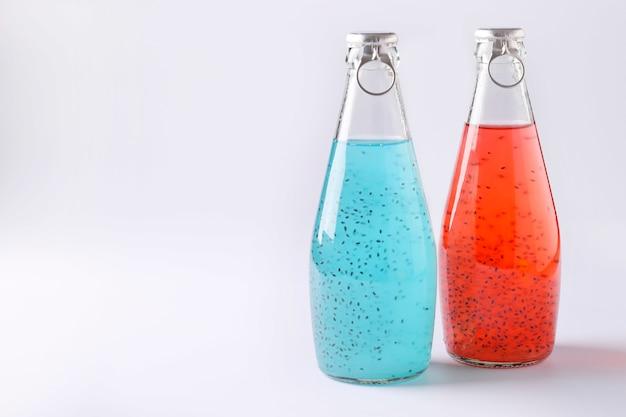 Bebidas azuis e vermelhas com sementes de manjericão ou sementes de falooda ou tukmaria em garrafas