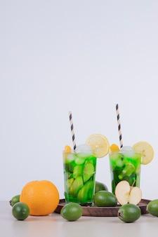 Bebidas com maçã, feijoa e canudo no branco