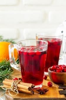 Bebidas de ação de graças de natal bebida quente de inverno com cranberries e canela na mesa de madeira