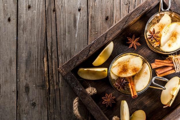 Bebidas de outono e inverno. cidra de maçã caseira tradicional, coquetel de cidra com especiarias aromáticas - canela e anis. em uma velha mesa rústica de madeira, em uma bandeja. vista superior do espaço da cópia