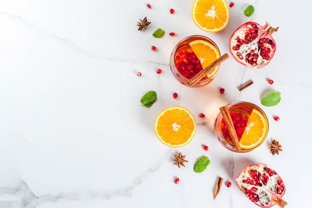 Bebidas de outono e inverno. cocktail refrescante quente com romã, laranjas, canela, especiarias e hortelã. em uma mesa de mármore branco. vista do topo