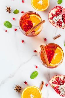 Bebidas de outono e inverno. cocktail refrescante quente com romã, laranjas, canela, especiarias e hortelã.