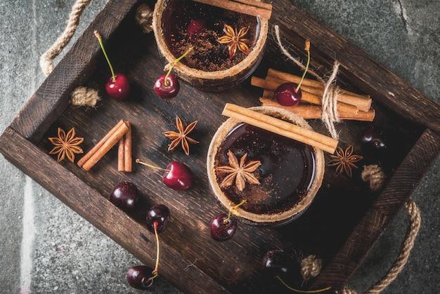 Bebidas de outono e inverno. sangria de cereja quente com canela, anis, vinho e especiarias. em uma pedra escura e de madeira com ingredientes,, na vista superior da bandeja