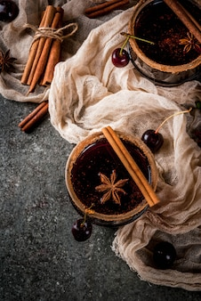 Bebidas de outono e inverno. sangria de cereja quente com canela, anis, vinho e especiarias. em uma pedra escura e de madeira com ingredientes, vista superior