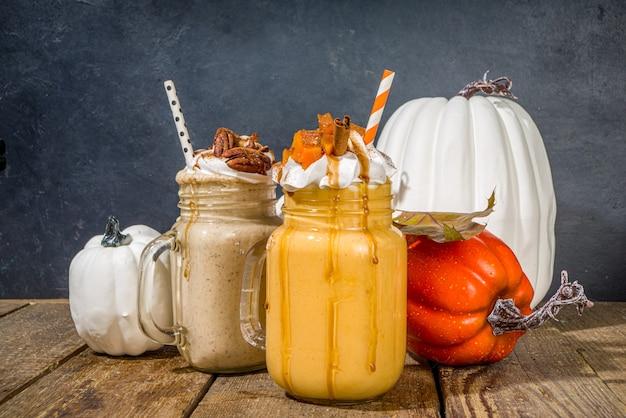 Bebidas de smoothie de torta de maçã, abóbora e noz-pecã. conjunto de coquetéis com sabor de bolo assado no outono tradicional, em um espaço de cópia de fundo escuro de madeira