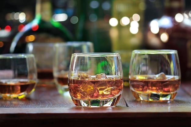 Bebidas de uísque com gelo no fundo de madeira