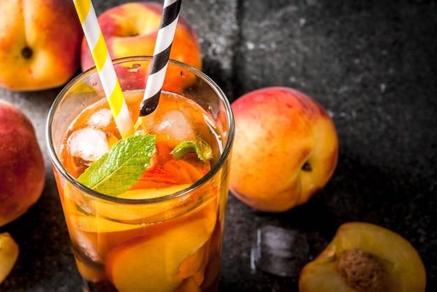 Bebidas de verão. chá gelado com pedaços de pêssego caseiro orgânico de nectarina. sobre um fundo preto de pedra, com gelo e ingredientes. copyspace vista próxima