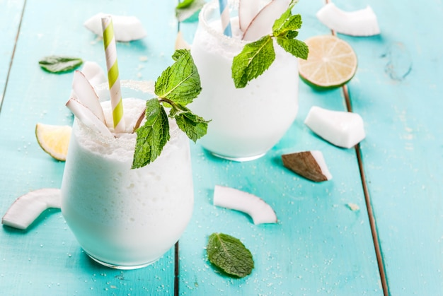 Bebidas de verão, coquetéis. mojito de coco congelado com limão e hortelã. piña colada. em uma mesa de madeira verde azul clara com ingredientes. copyspace