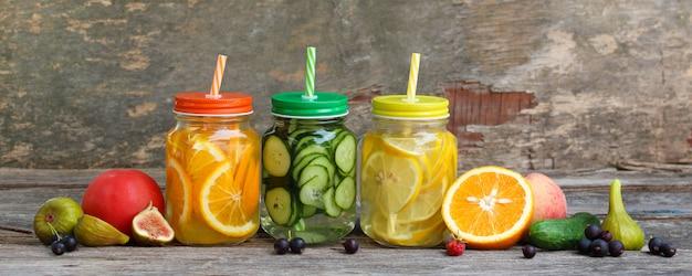 Bebidas diferentes, frutas e legumes no fundo de madeira.