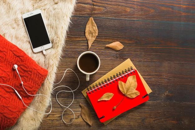Bebidas e blocos de notas perto de camisola e smartphone