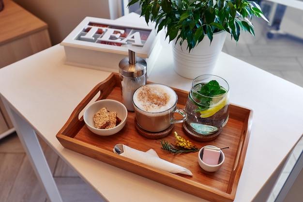 Bebidas e comida em uma bandeja de madeira, café e limonada com doces, uma caixa de chá