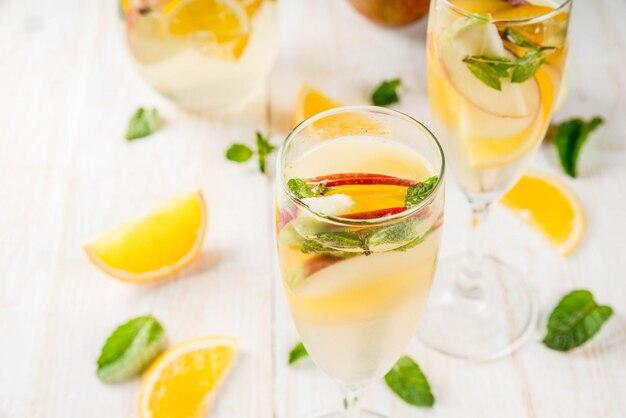 Bebidas e coquetéis. sangria de outono branca com maçãs, laranja, hortelã e vinho branco. em copos de champanhe, em uma jarra, em uma mesa de madeira branca. copie o espaço