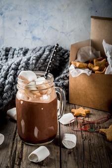 Bebidas e guloseimas tradicionais de inverno outono. xícara de chocolate quente com estrelas de biscoito de marshmallow e gengibre, em caixa de presente, velha mesa de madeira rústica. atmosfera acolhedora, espaço para texto
