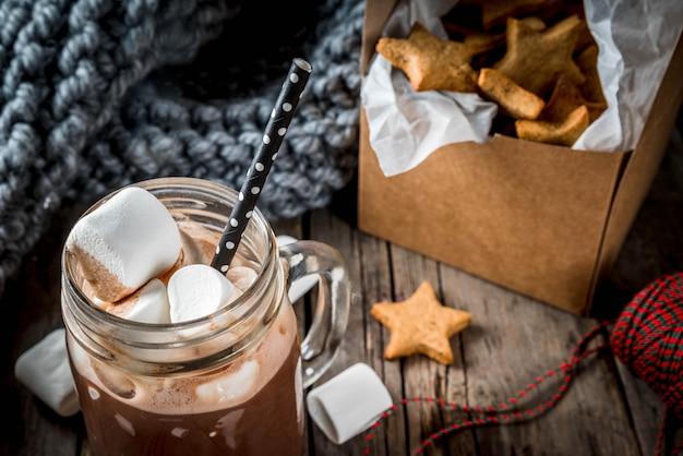 Bebidas e guloseimas tradicionais de inverno outono. xícara de chocolate quente com estrelas de marshmallow e biscoito de gengibre