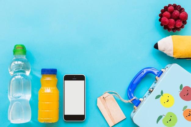 Bebidas e smartphone perto de lancheira e estojo