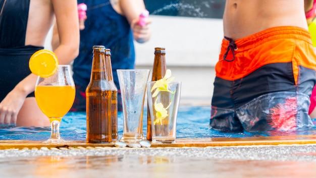 Bebidas e sucos com coquetéis exóticos e garrafa de cerveja montada na piscina.