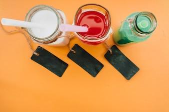 Bebidas em garrafas de vidro com canudos ao lado de rótulos escuros