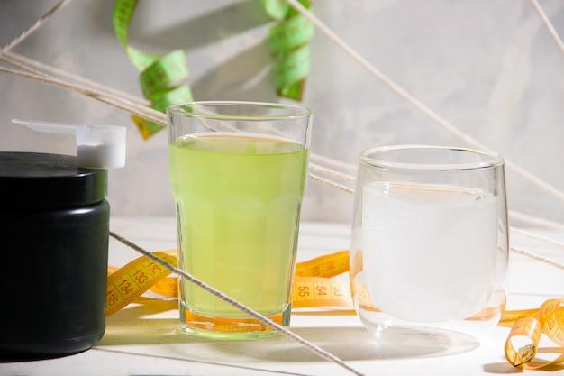 Bebidas esportivas em copos em um fundo cinza.