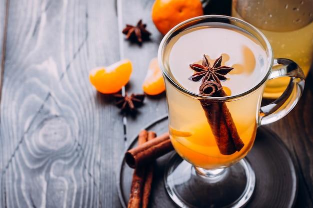Bebidas frescas com especiarias, frutas cítricas e canela em vidro na madeira