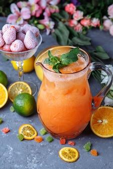Bebidas frescas no verão de bebidas frias. limonada de gelo no jarro e limões e laranja com hortelã na mesa ao ar livre.