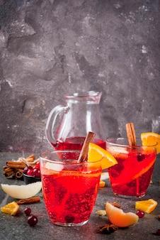 Bebidas frias de outono e inverno, cranberry e laranja férias soco de natal com canela, estrelas de anis, na copyspace preto